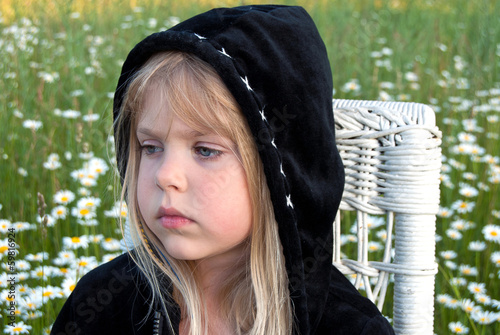sad little girl wearing a black hoodie