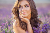 Fototapety Beautiful young woman relaxing in a lavender field at sunset