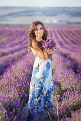 Beautiful young woman relaxing in a lavender field at sunset