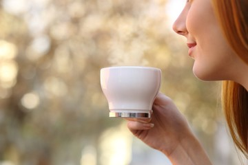 Close up of a woman holding a coffee cup