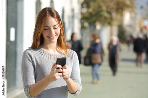 Woman in the street browsing a smart phone