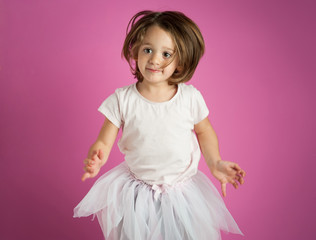 Young dancer girl portrait against pink background.