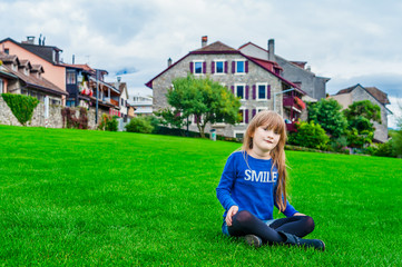 Cute little girl sitting on a bright green lawn