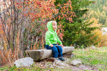 Cute toddler boy resting in a forest