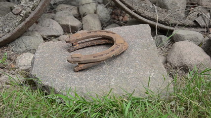 hand make stack of rusty retro horse shoes on stones background