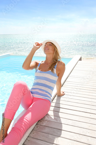 Blond woman with hat relawing by pool