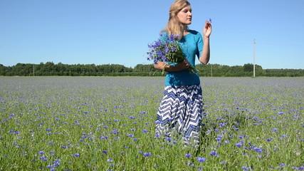 Elegant lady pick bouquet of blue cornflower flowers in field