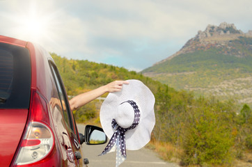 Woman shows sun hat from car