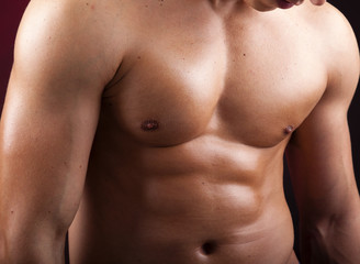 Cropped image of a beautiful man torso against black background