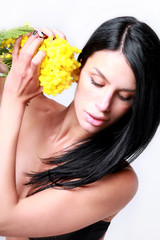 Sensual brunette girl with mimosa flower