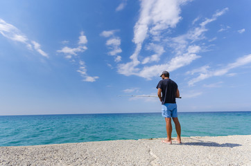 Man fishing on seaside horizon. Clear water and blue sky.