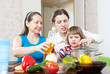 woman and adult daughter with child cook vegetables
