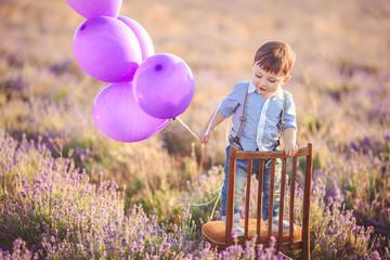 Little fashionable boy having fun in lavender summer field.