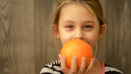 little girl holding an orange