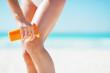 Closeup on woman applying sun screen creme on beach