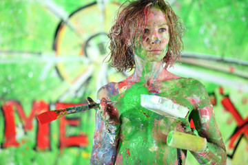 Naked girl with brush and roller in hand covered in paint