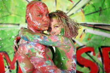 Naked girl hug bald man all in the paint in studio