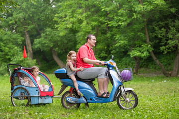 Father with three children drive on unreal design scooter