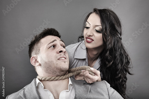 Man being tied by his neck with a rope by a woman