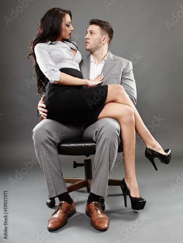 Secretary sitting on the boss lap