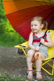 Little girl with grimy legs sitting on chair with umbrella
