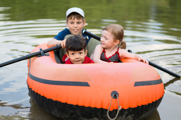 Three children float on boat with oars, focus on little boy.