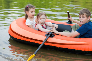 Three children floating in a rubber boat on the pond