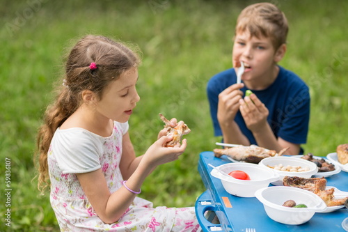 Boy and girl eat meat with vegetables at the picnic