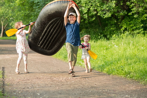 happy children carry boat with oars on footpath