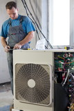 worker in workwear sets air conditioner in apartment poster