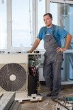 worker in workwear sets air conditioner in new apartment poster