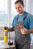 Worker in workwear welds copper tube oxyfuel gas welding poster