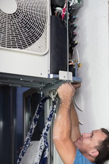 A worker sets split system air conditioner outdoor
