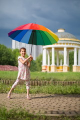 Smiling girl with umbrella on nature with beautiful arbor