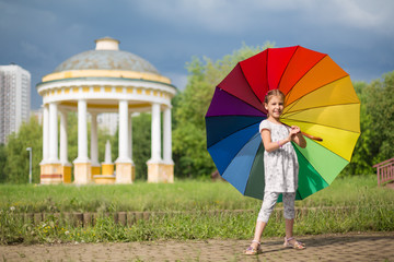 Little girl with umbrella on nature with beautiful arbor