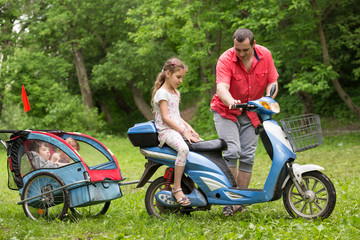 Father and children on scooter with cart on nature