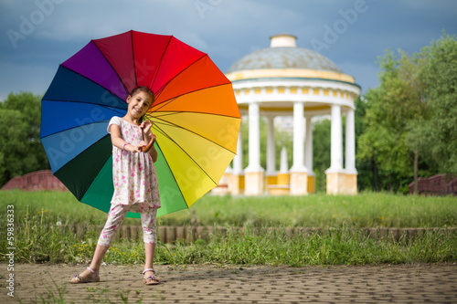 Girl with umbrella on nature with a beautiful arbor