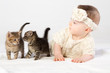 Baby girl dressed in fur plays with two little kittens