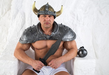 A muscular man in costume viking with a sword
