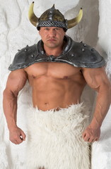 A muscular man in costume viking with a fur