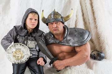 A muscular man with son in costume viking with a sword