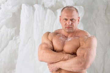 A strong man with big muscles with snow on body