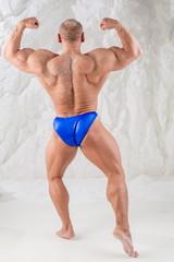 Male bodybuilder in trunks posing back in studio