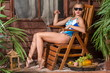 girl in swimsuit sunbathing on wooden chair with fruit