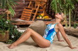 Beautiful girl in swimsuit sunbathing on sandy beach