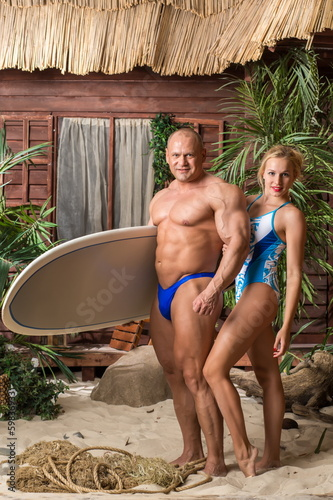 Muscular man in trunks and girl in swimsuit with surfboard