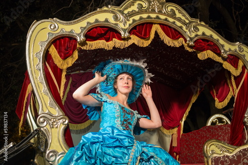 girl in old-fashioned dress correct the hat in carriage