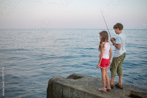 boy an girl with a fishing rod fishing in the sea