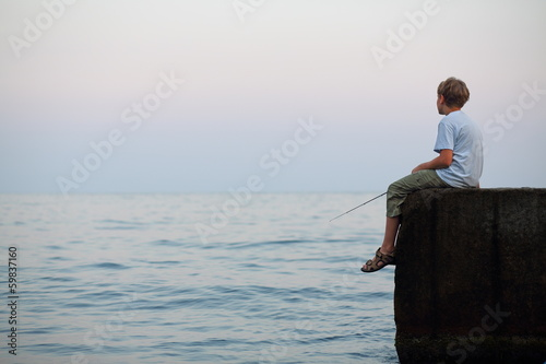 boy with fishing rod sitting on rock and fishing in sea