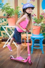Little girl in helmet riding scooter on wooden floor in cafe